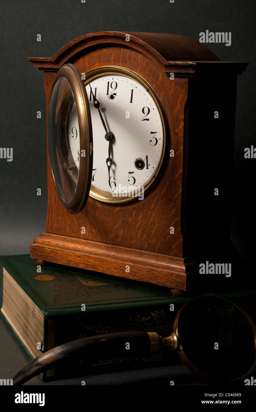 Seth Thomes clock sat on top of a book, as its galss door is open - Stock Image