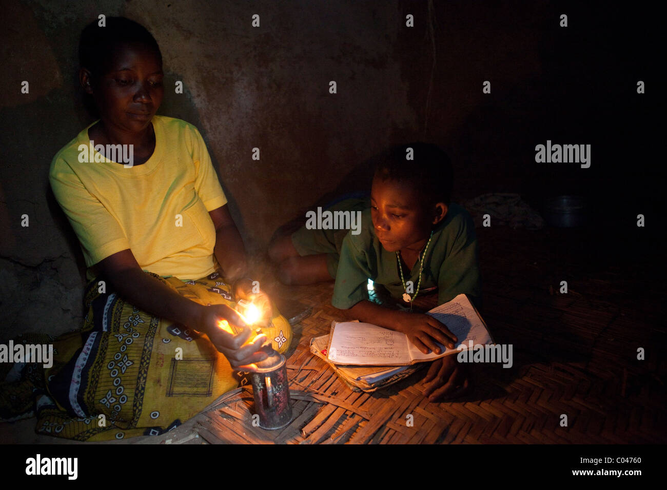 A mother lights a small lamp for her child to study by in Masaka, Uganda, East Africa. Stock Photo