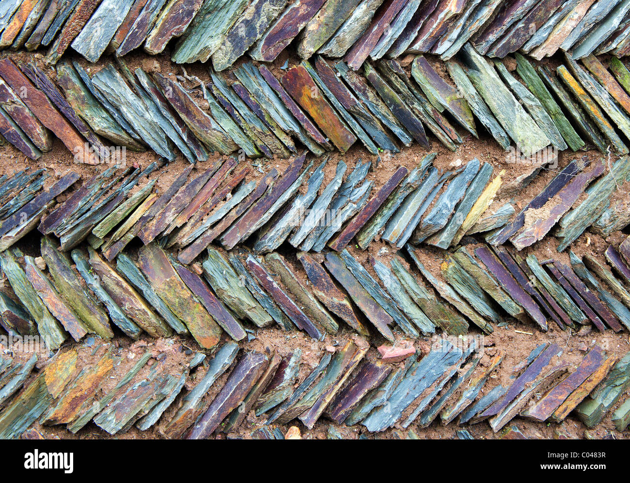 The detail and pattern in a herring bone design stone garden wall - Stock Image