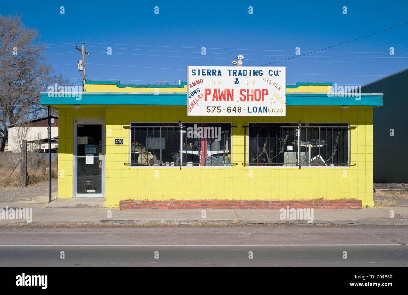 The bright yellow building of Sierra Trading Company pawn shop in Carrizozo, New Mexico. - Stock Image