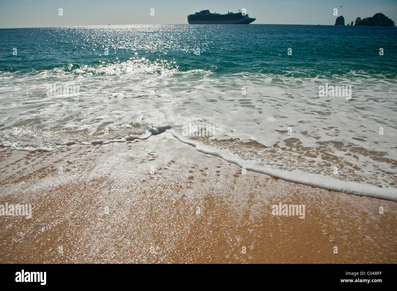 Gentle waves crushing up a  tropical sandy beach with a cruise ship in the background - Stock Image