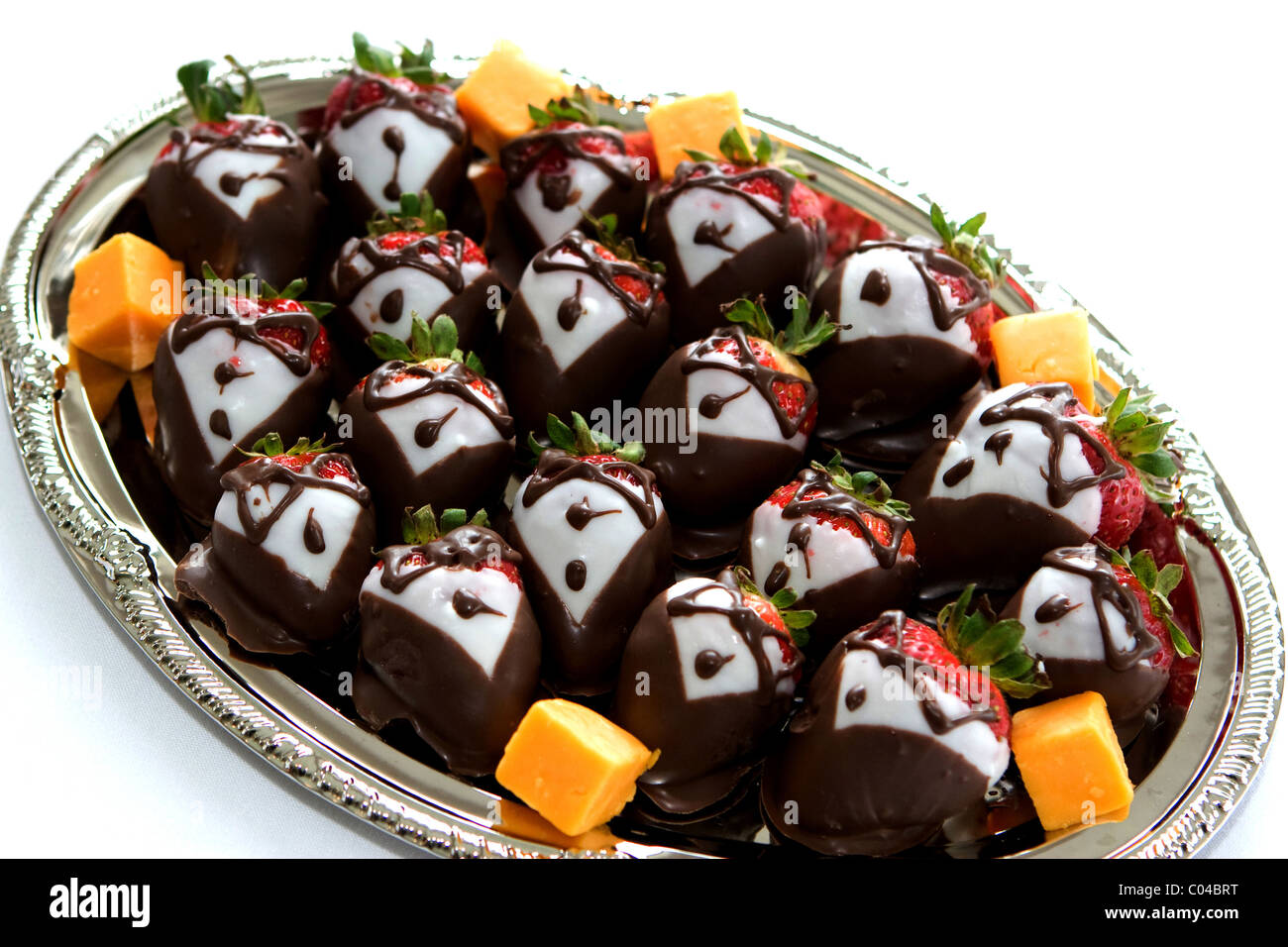 A platter of strawberries are decorated in dark and white chocolate to look like they are dressed in tuxedos. - Stock Image