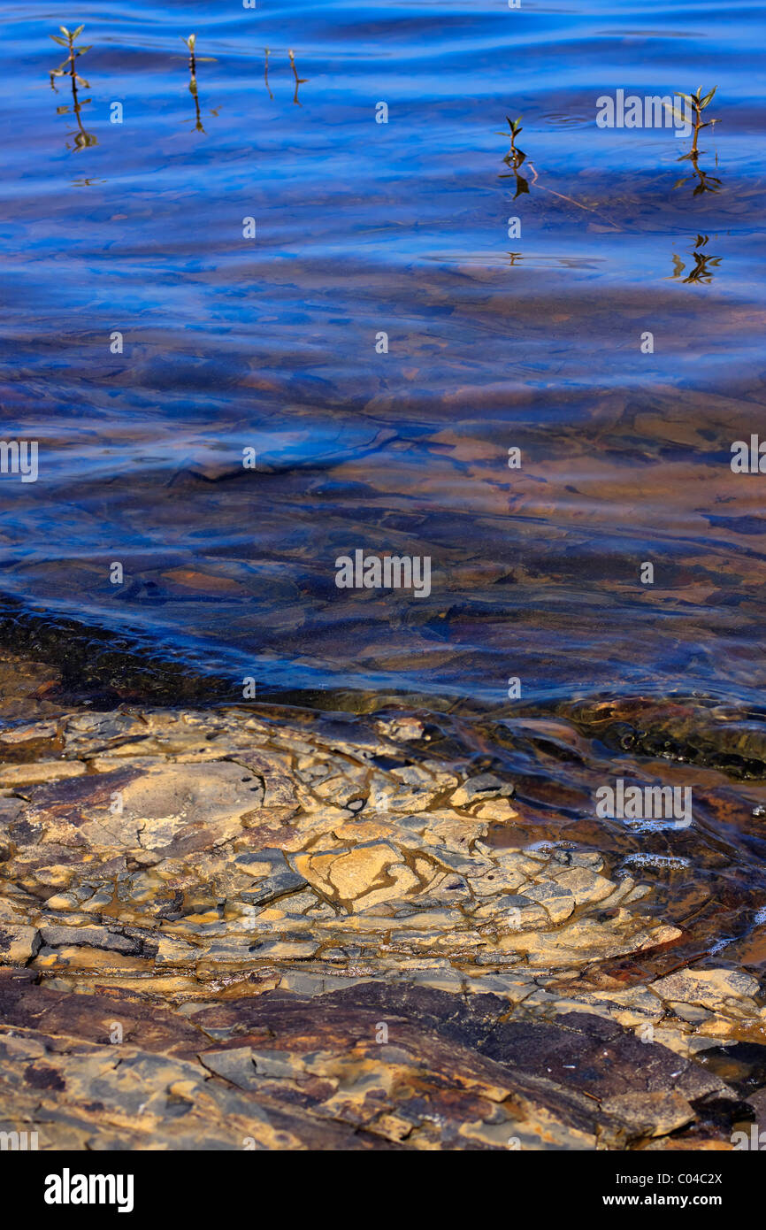 Reflections of the sky in the water lapping rocks at lake's edge. - Stock Image