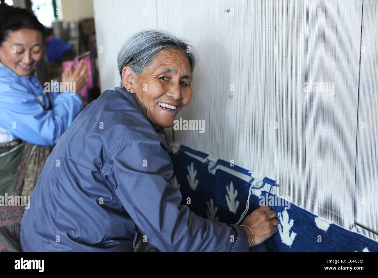 Tibetan Woman in Exile weaving Rugs in McLeod Gange, India - Stock Image