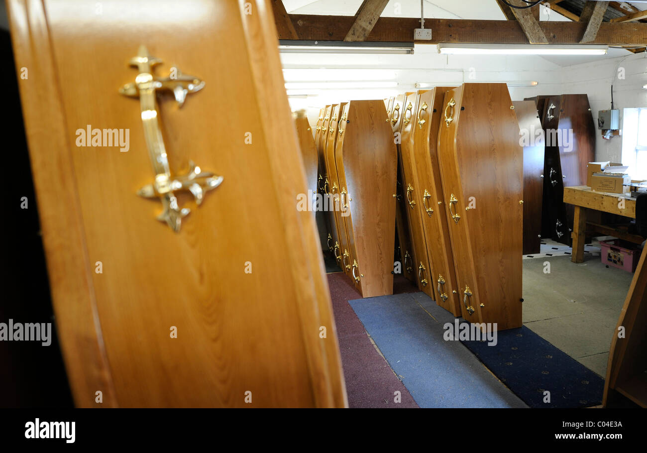 Caskets in a coffin maker's workshop at a funeral director in the UK. - Stock Image