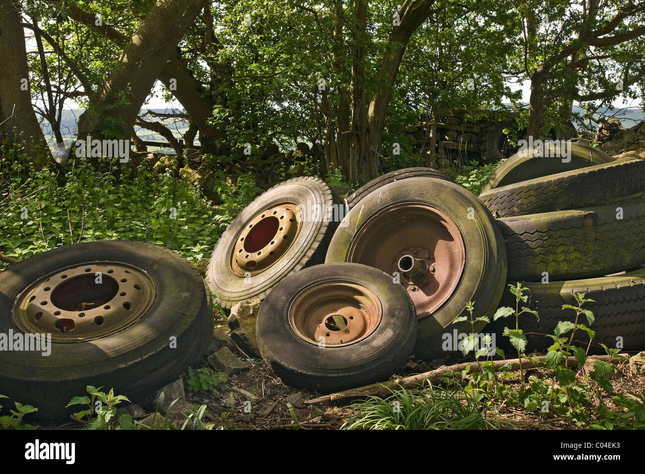 A collection of tyres and old wheels dumped alongside a country lane in North Yorkshire - Stock Image