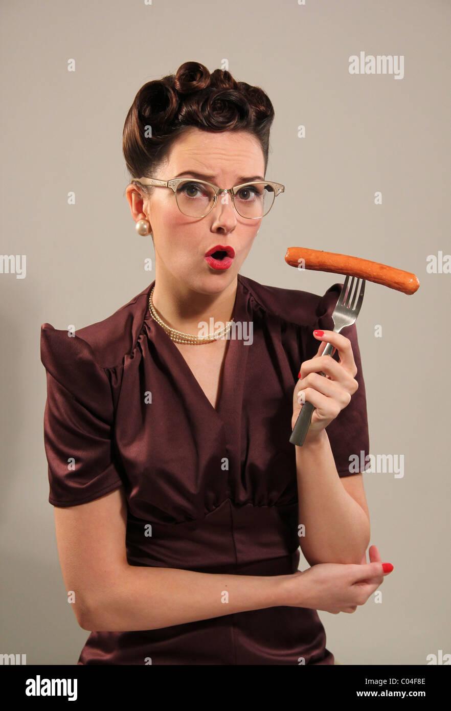 Retro woman holding a sausage - Stock Image