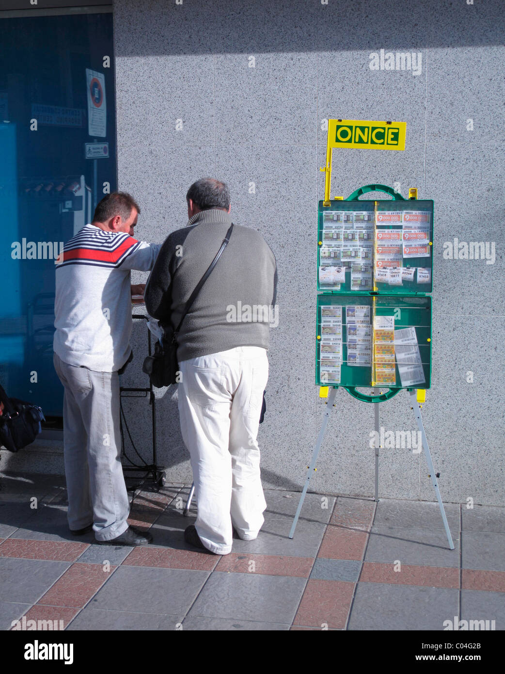 Blind lottery ticket seller belonging to ONCE organization selling ticket to client. - Stock Image