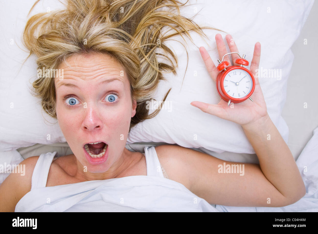Woman in bed realizing that she has slept in despite having an alarm clock - Stock Image