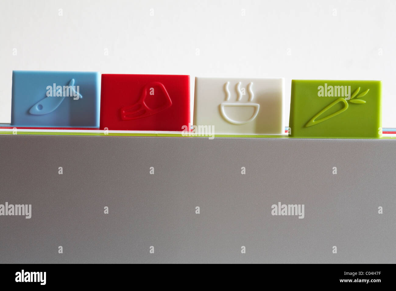 Multi purpose colour coded chopping boards on white background - Stock Image