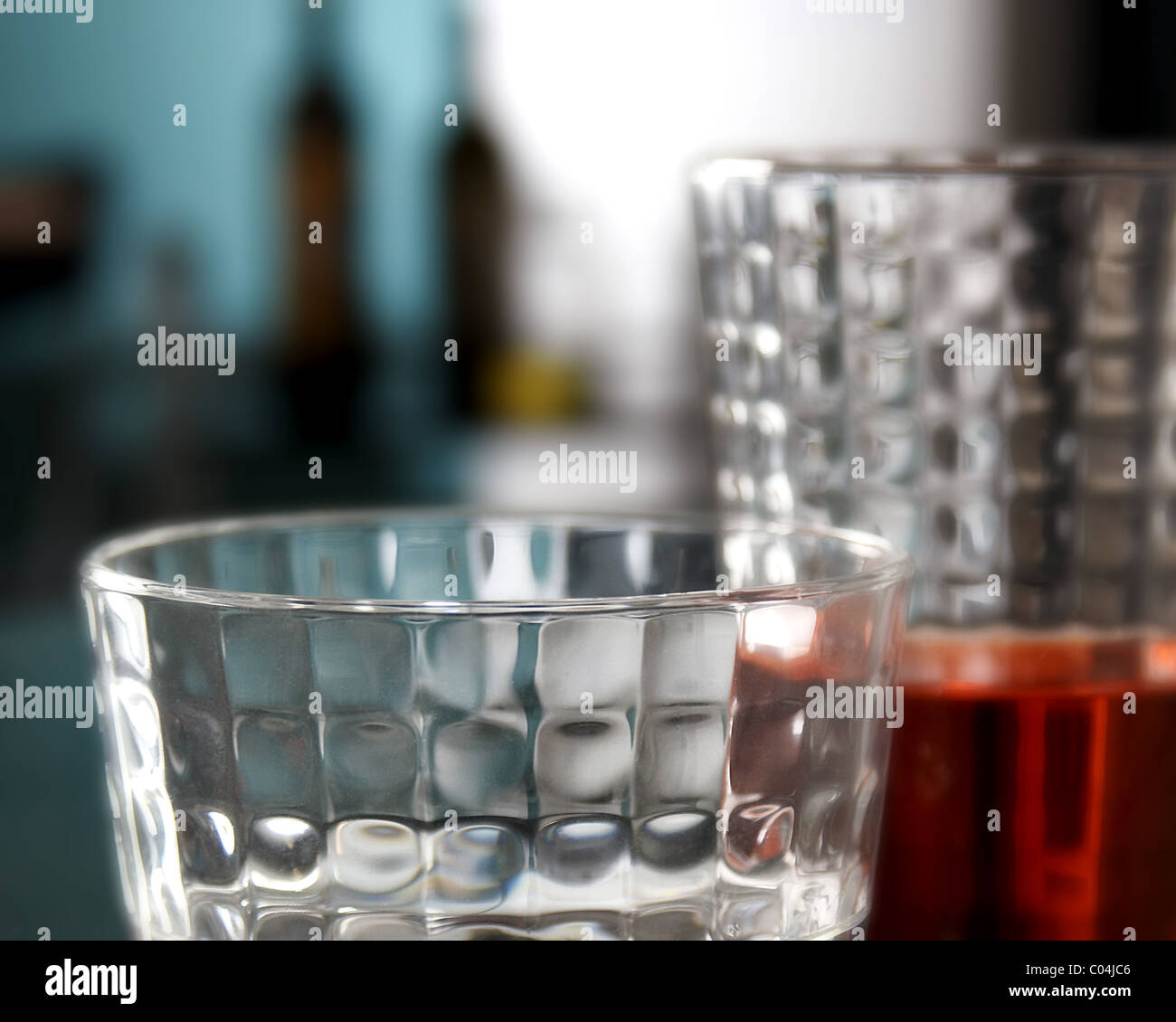 glasses of red drink and bottles in the background - Stock Image