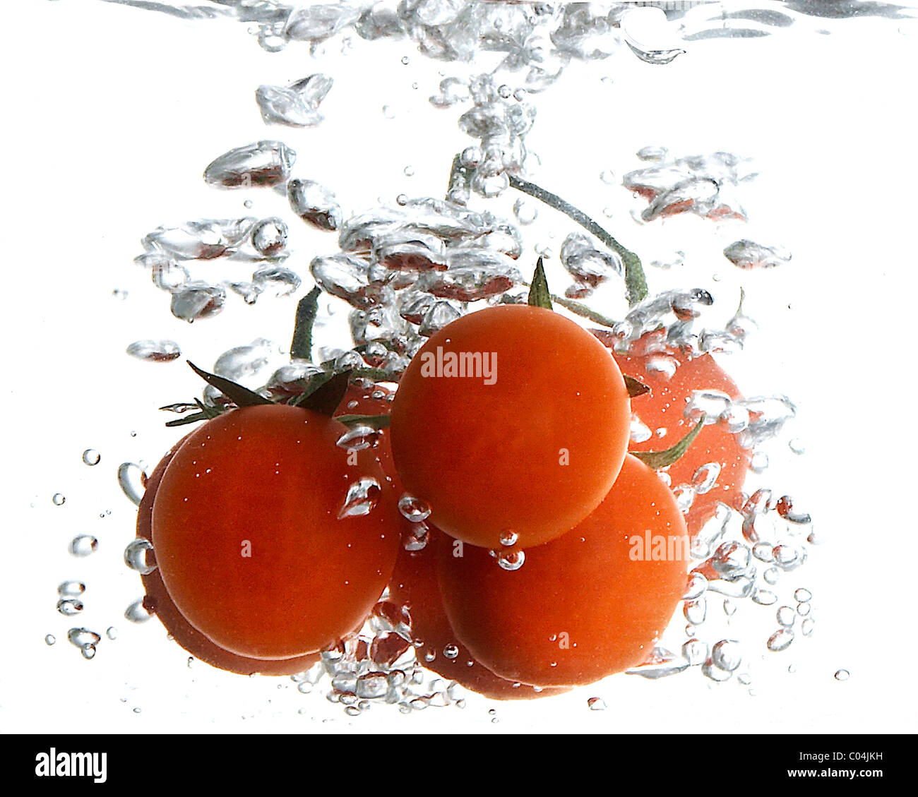 Some red round tomatoes in the water - Stock Image