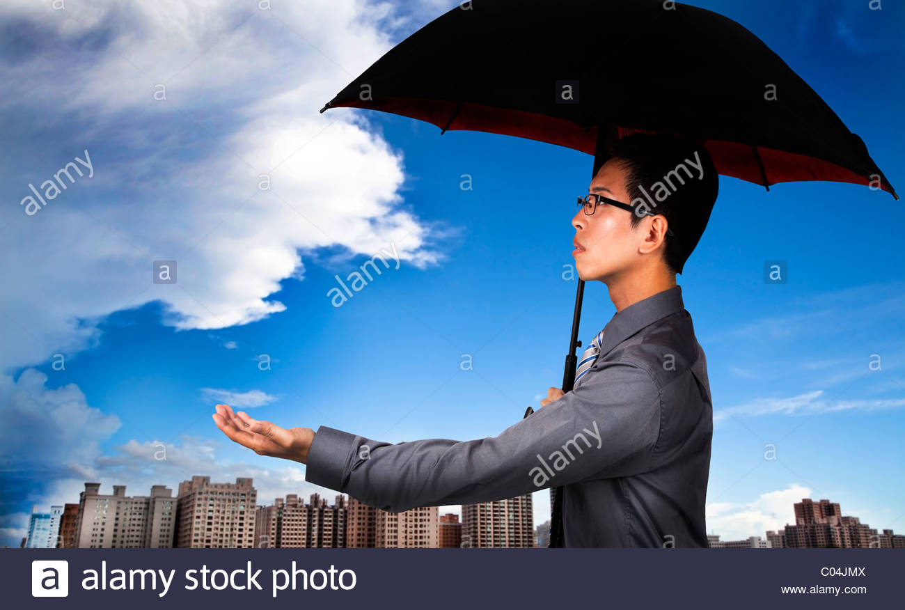 The insurance agent with umbrella and Weather Observation - Stock Image