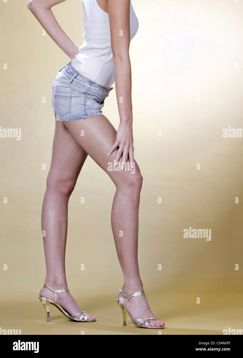 legs of a woman on yellow background Stock Photo