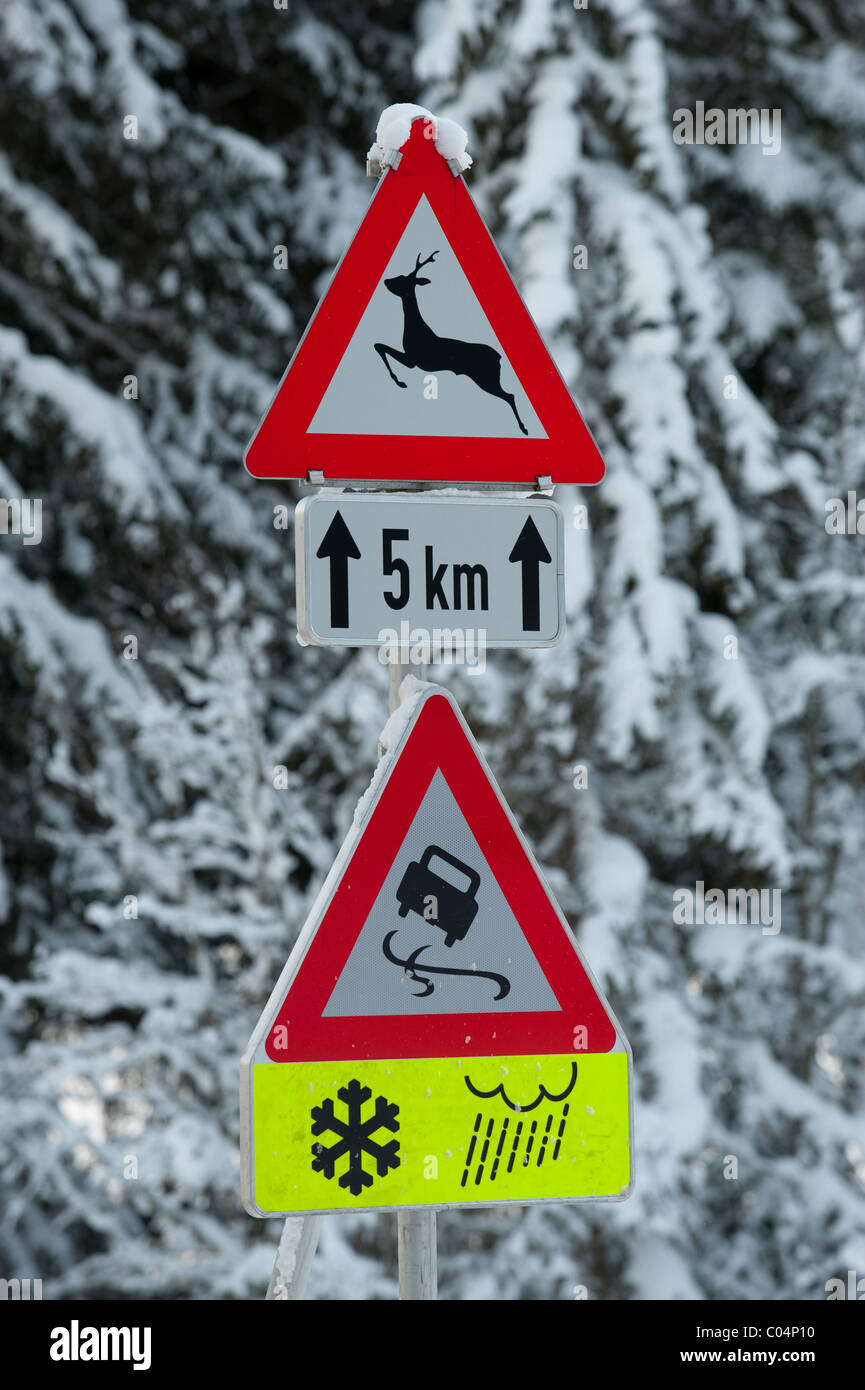 traffic sign warns at winter of snow and ice on slippery road - Stock Image