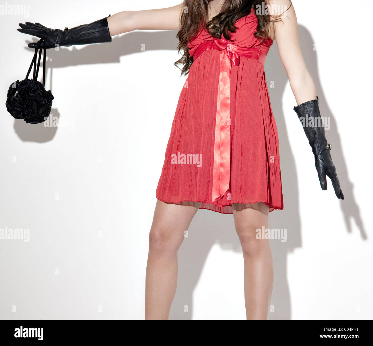 Woman in red dress back gloves and black handbag Stock Photo