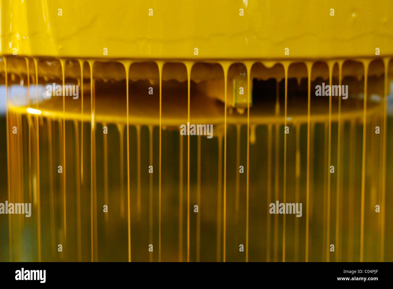 Industrial machinery for paint working with yellow paint Stock Photo