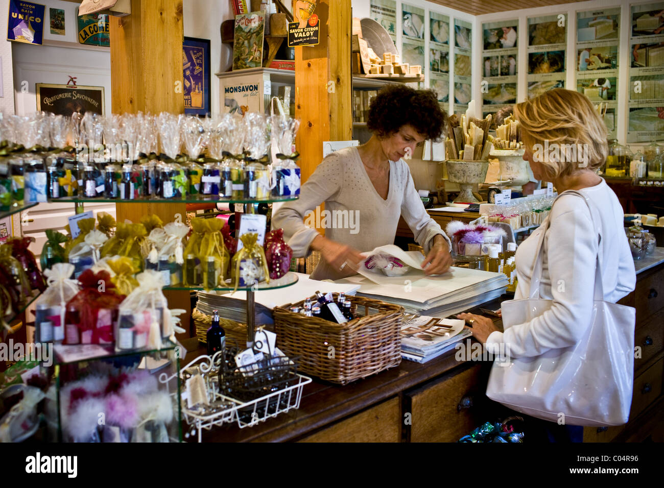 Shopper buying at artisan soaps Martin de Candre specialist savon shop Mestre at Fontevraud L'Abbaye, Loire - Stock Image
