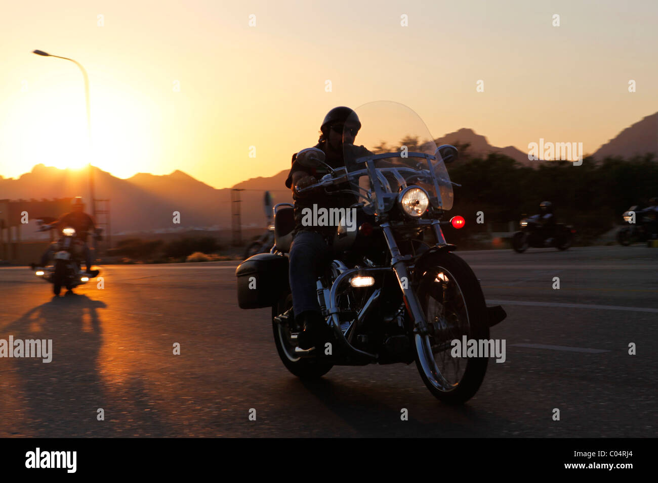 A group of Harley-Davidson bikers rides out into the desert as the sun sets. - Stock Image