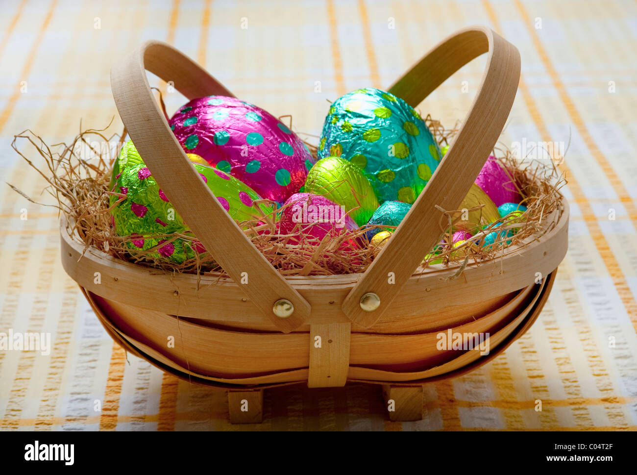 Small traditional wooden basket filled with hay and colorful wrapped chocolate easter eggs on a yellow and white Stock Photo