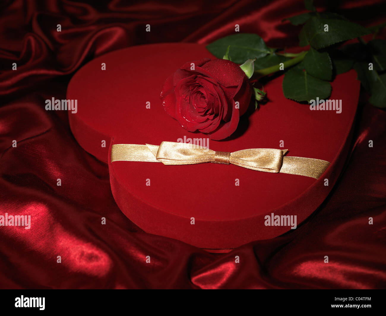 Red heart-shaped gift box and a red rose - Stock Image