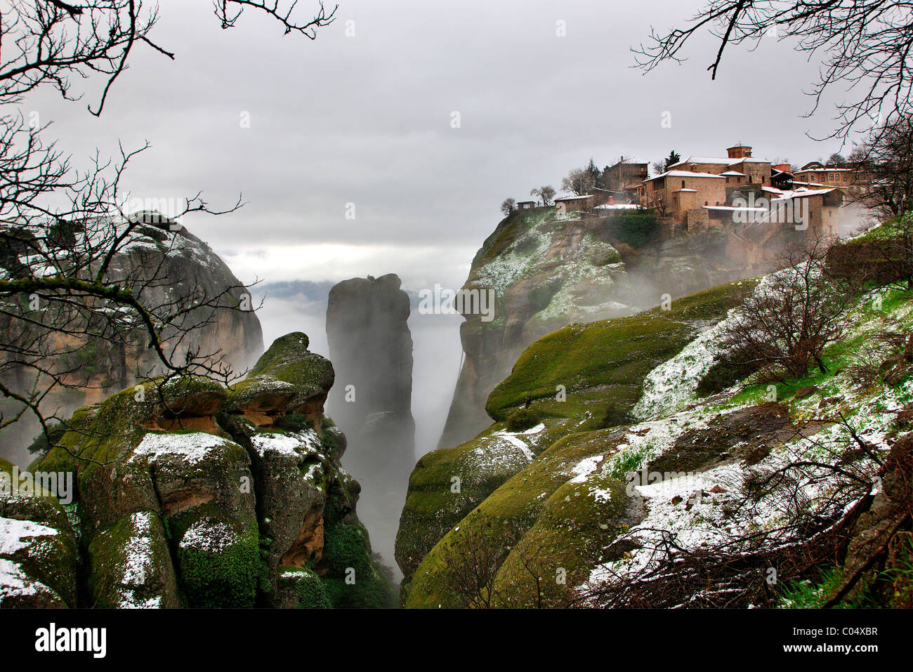 Greece, Meteora. Winter atmosphere with fog and snow. On the upper right part the Great  Meteoron monastery. - Stock Image