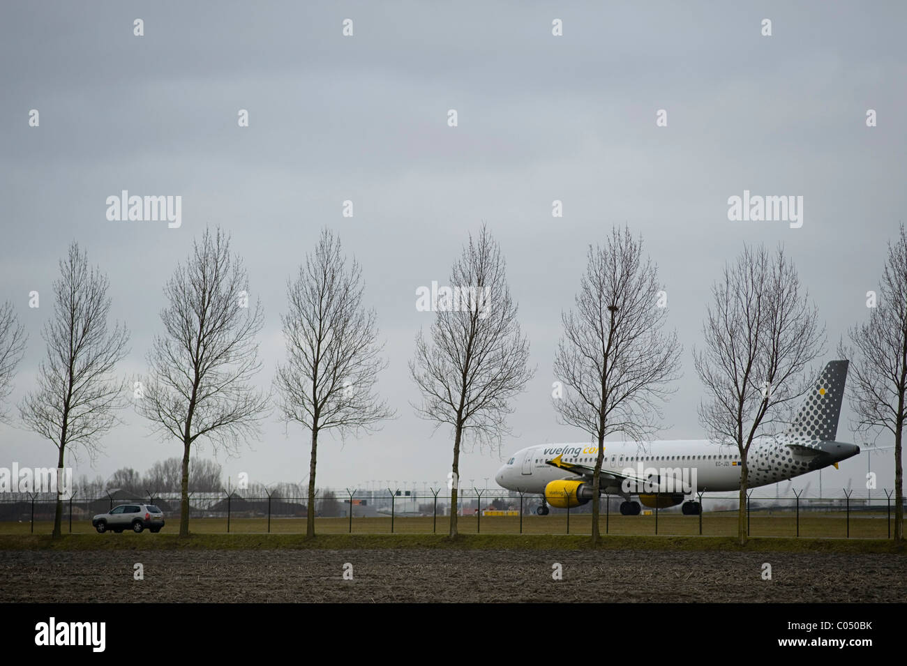Airplane taxiing alongside car at Schiphol Airport Amsterdam - Stock Image