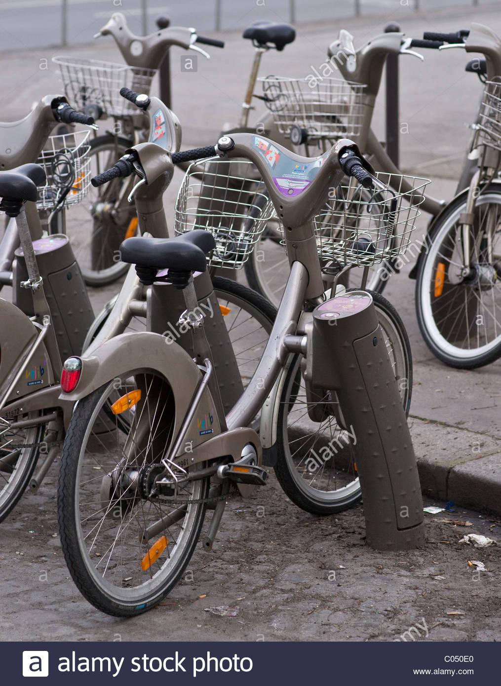 People riding bikes bicycles Paris France - Rent rental bikes - Stock Image