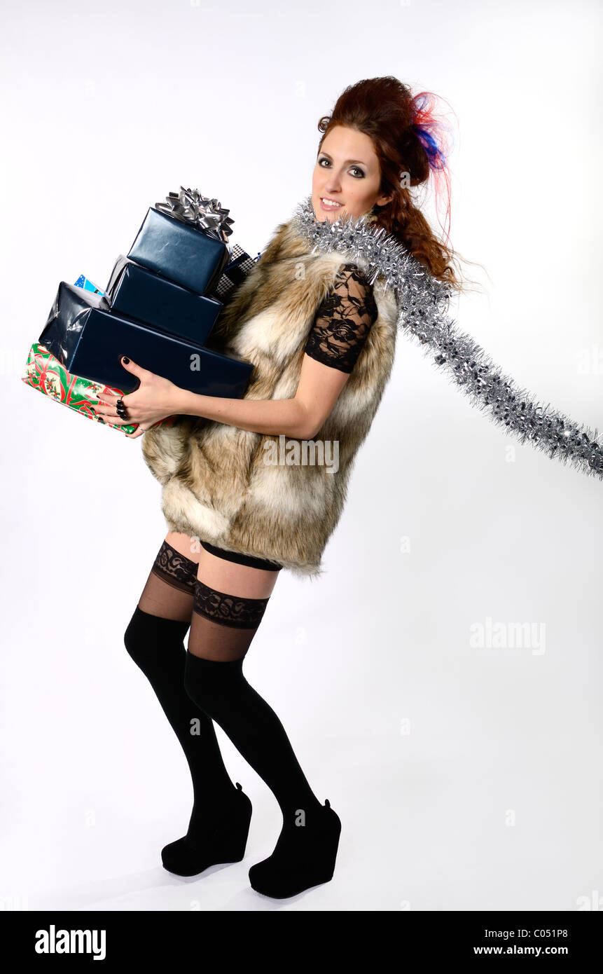 Tall elegant woman in miniskirt and Fur carrying armload of gift wrapped presents - Stock Image