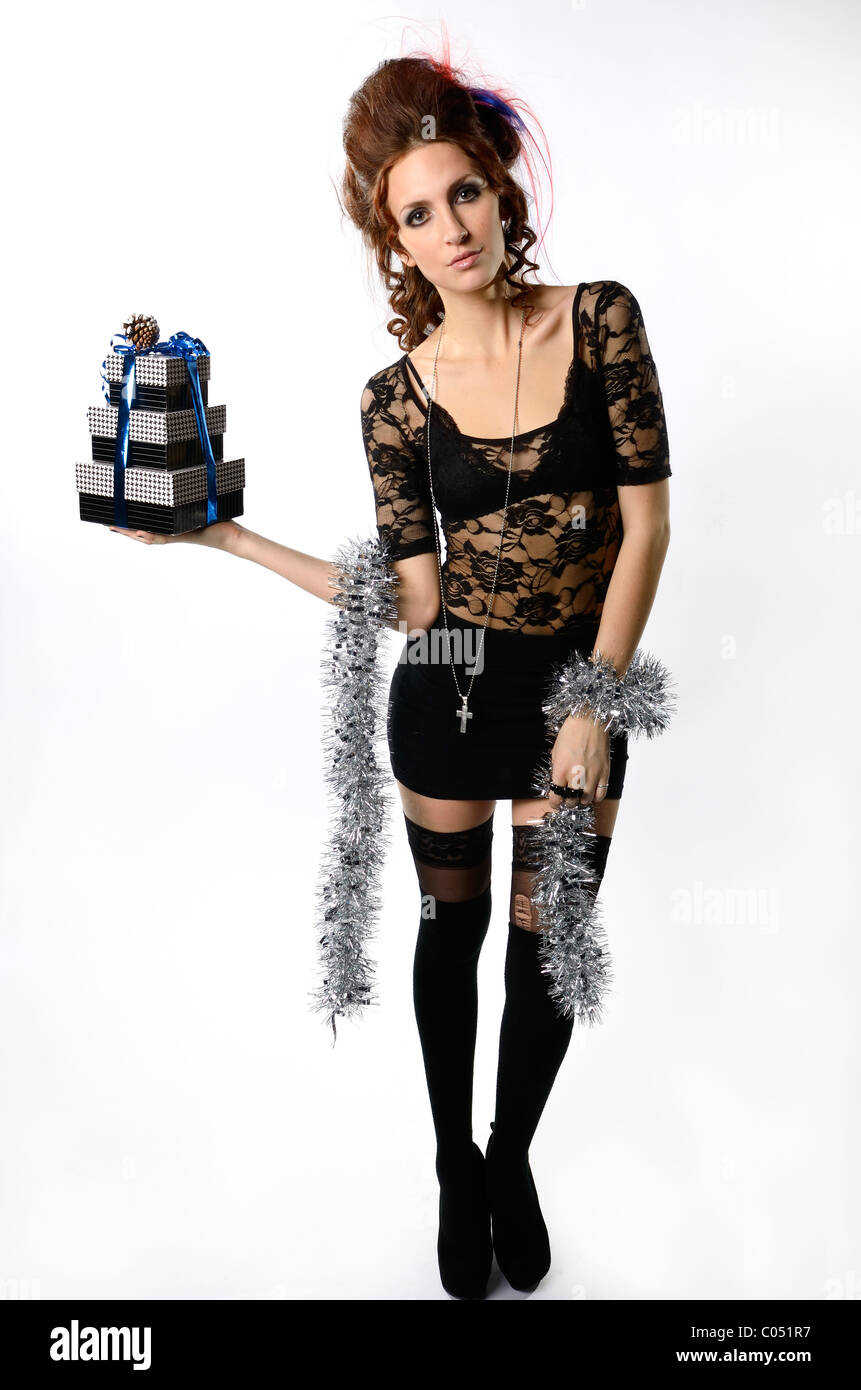 Tall elegant woman in black lace and miniskirt holding gift wrapped boxes on white background - Stock Image