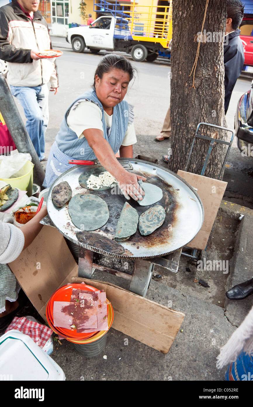 busy genial Mexican cook in spotless blue gingham apron working over her grill of blue corn tacos on sidewalk  of Stock Photo
