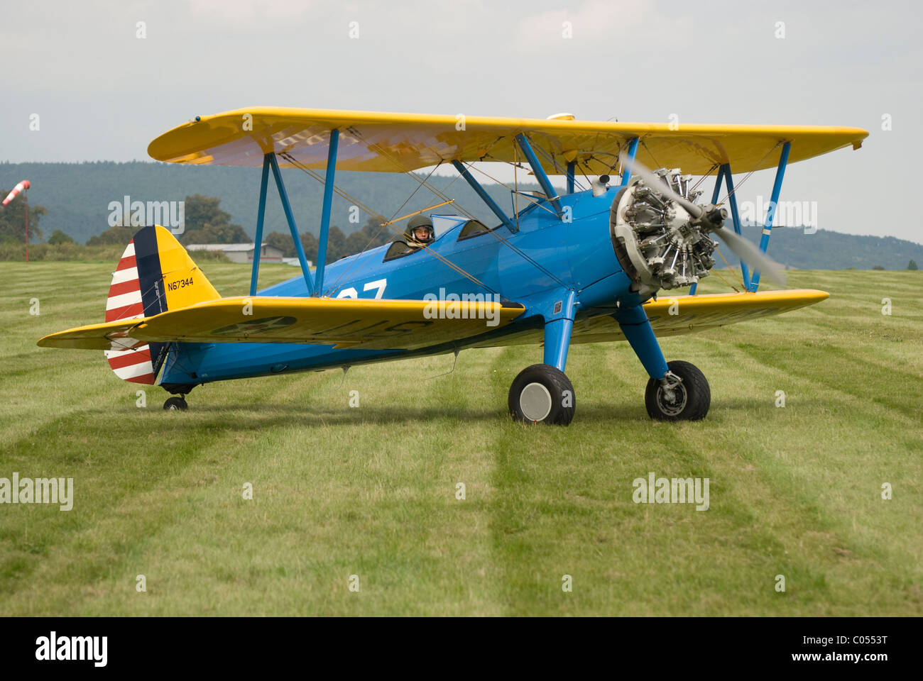 Biplane with radial engine - aircraft of type Boeing Stearman E75 on the ground, taxiing. - Stock Image