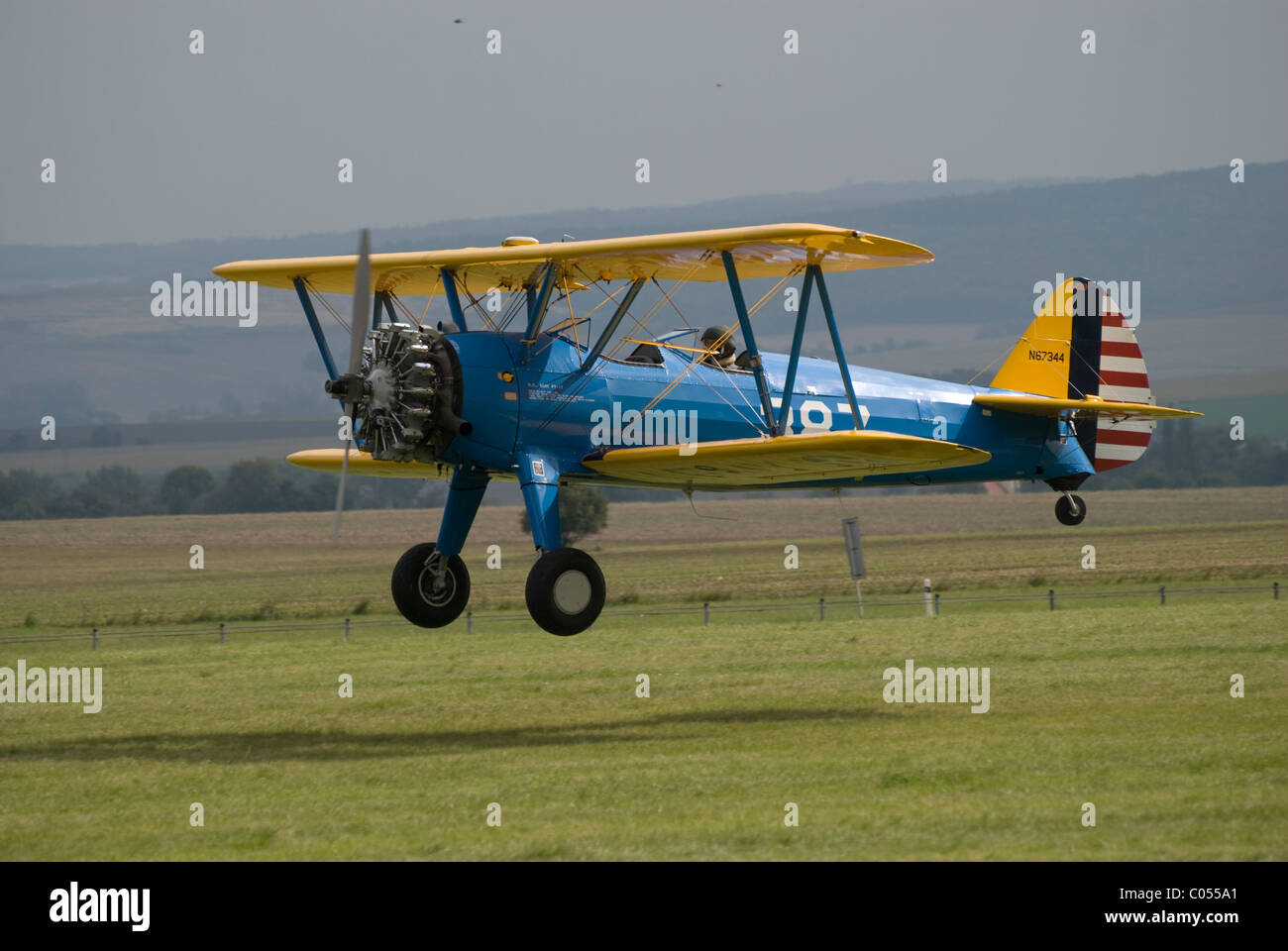 Biplane with star engine low pass - aircraft of type Boeing Stearman E75 is landing on grass airfield - Stock Image