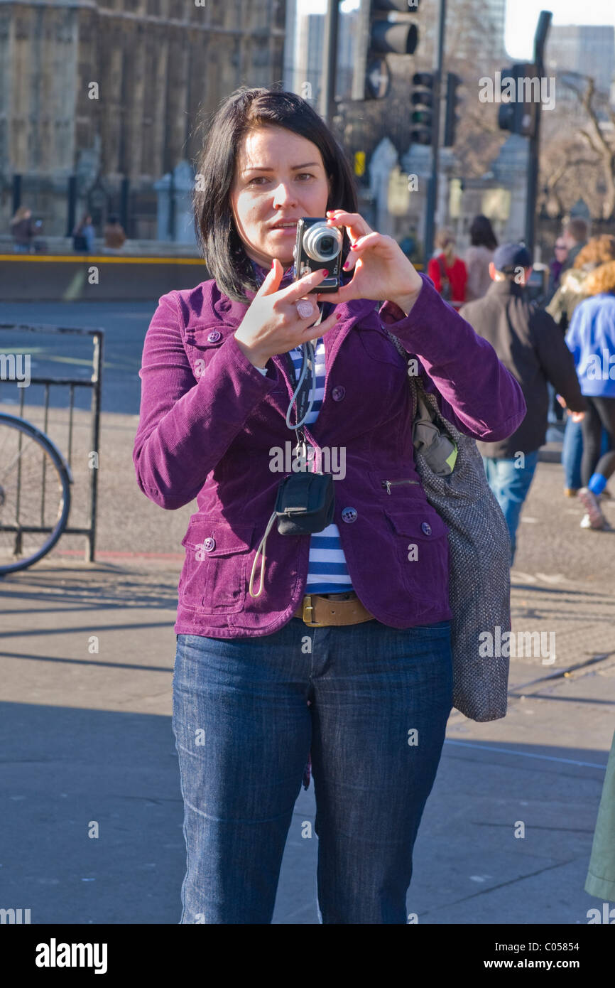 London , pretty young brunette lady or girl in jeans takes photo of London Eye from Westminster Bridge on Lumix - Stock Image