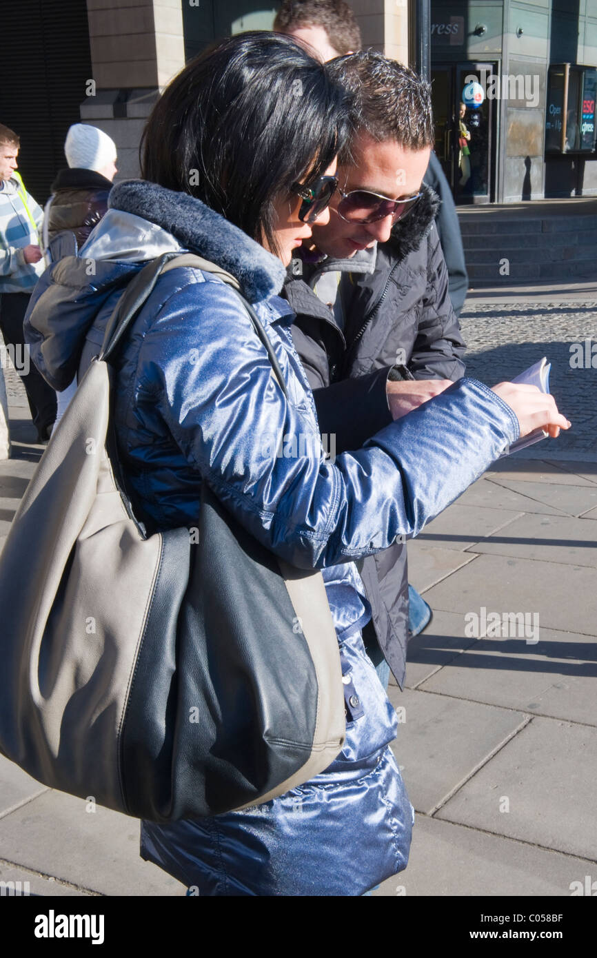 London , Westminster , Parliament Square , young couple in sunglasses , tourists check out guide book - Stock Image