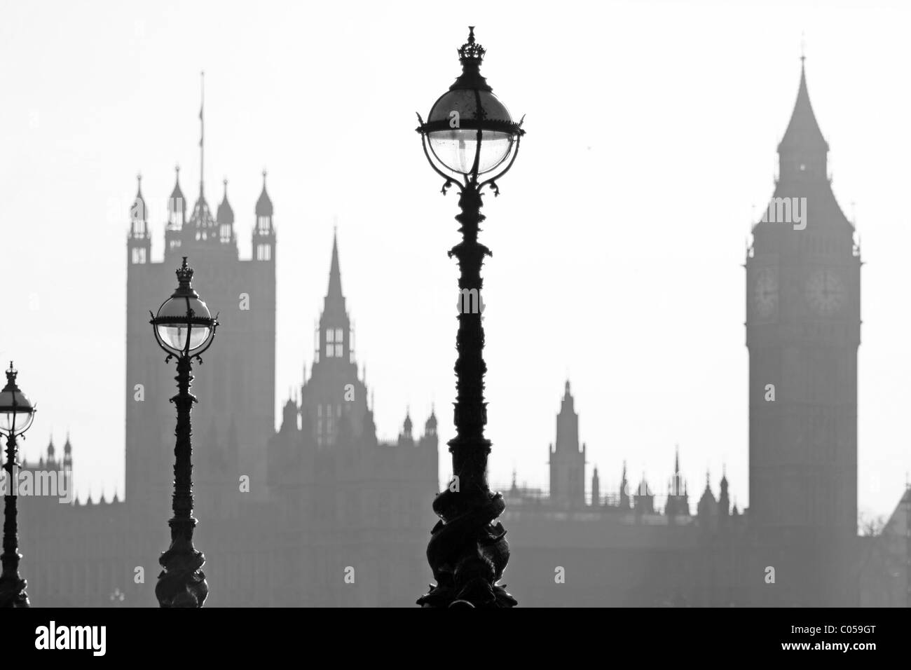 Silhouttes of Street lights on the embankment of the River Thames in London with The Houses of Parliament in the - Stock Image