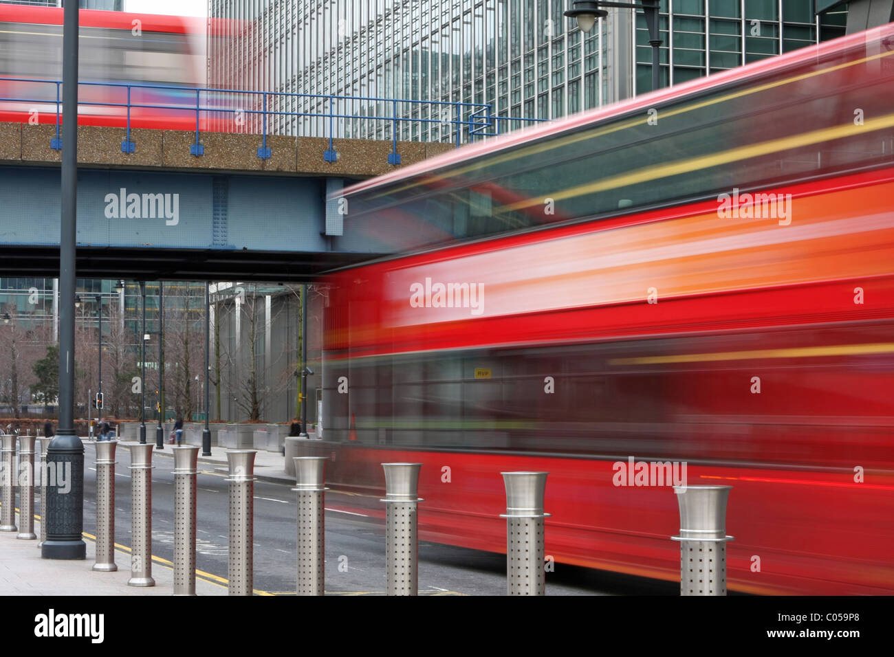 A blurred bus going under a bridge and a blurred DLR train going over the bridge in London's Canary Wharf Stock Photo
