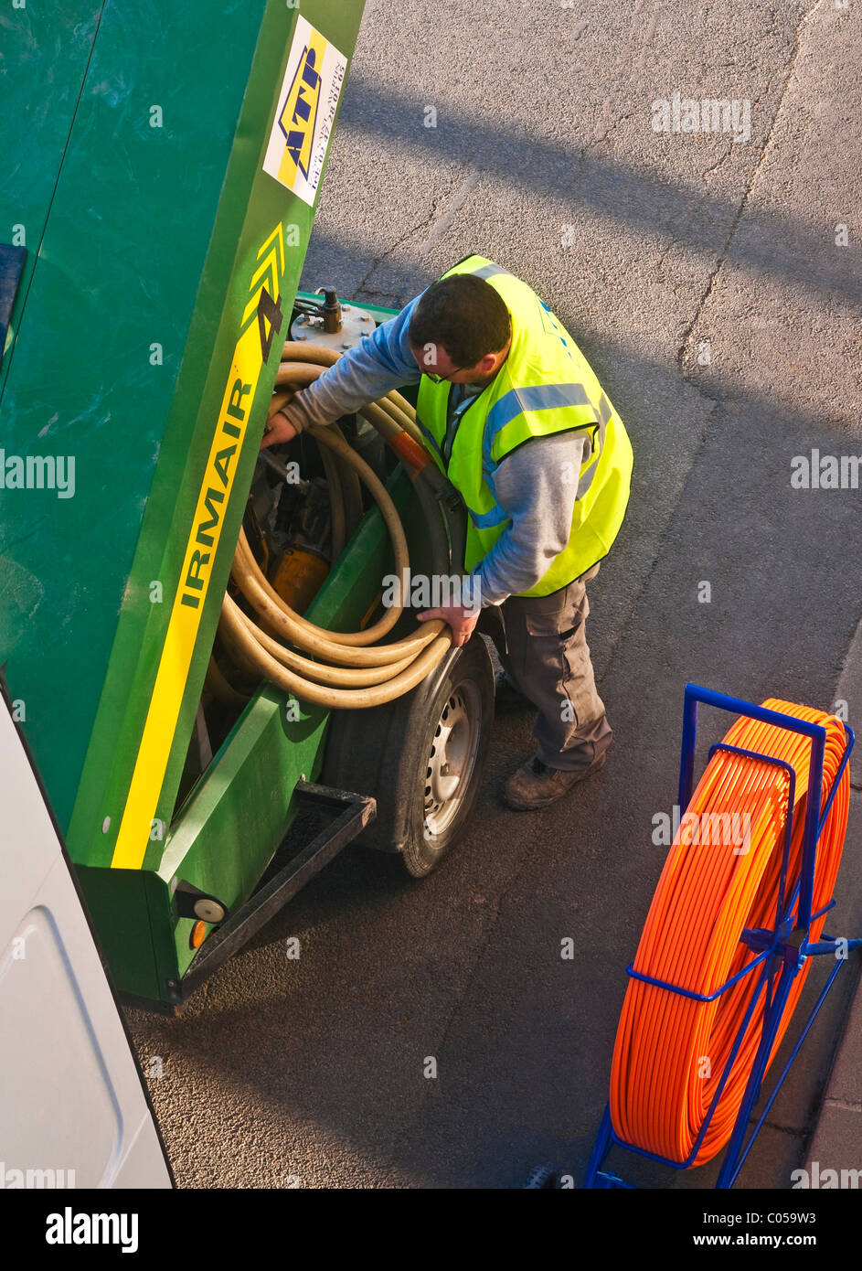 Workman in street coiling pipe - France. - Stock Image