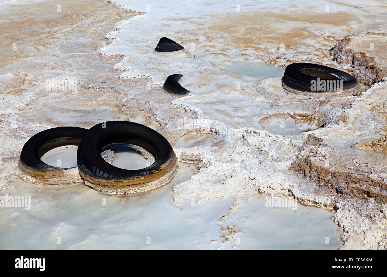 Dumped car tyres set in tufa water pollution in Brook Bottom Springs Buxton Peak District Derbyshire UK - Stock Image