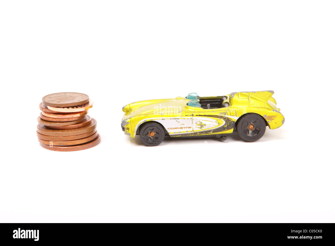 Old toy Corvette car with pile of penny pennies coins the cost of motoring - Stock Image