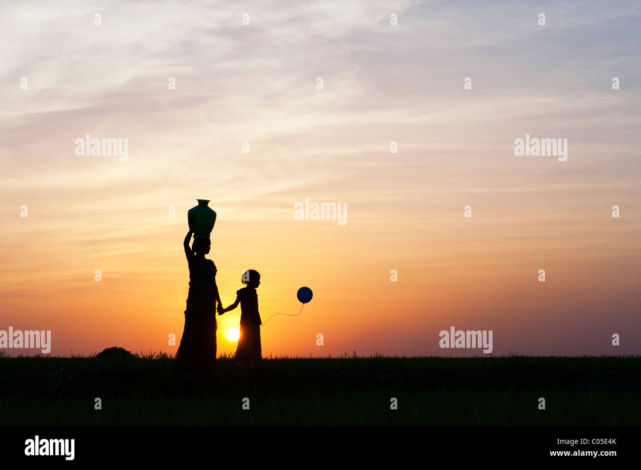 Indian mother carrying water pot with child and balloons in the indian countryside. Silhouette - Stock Image