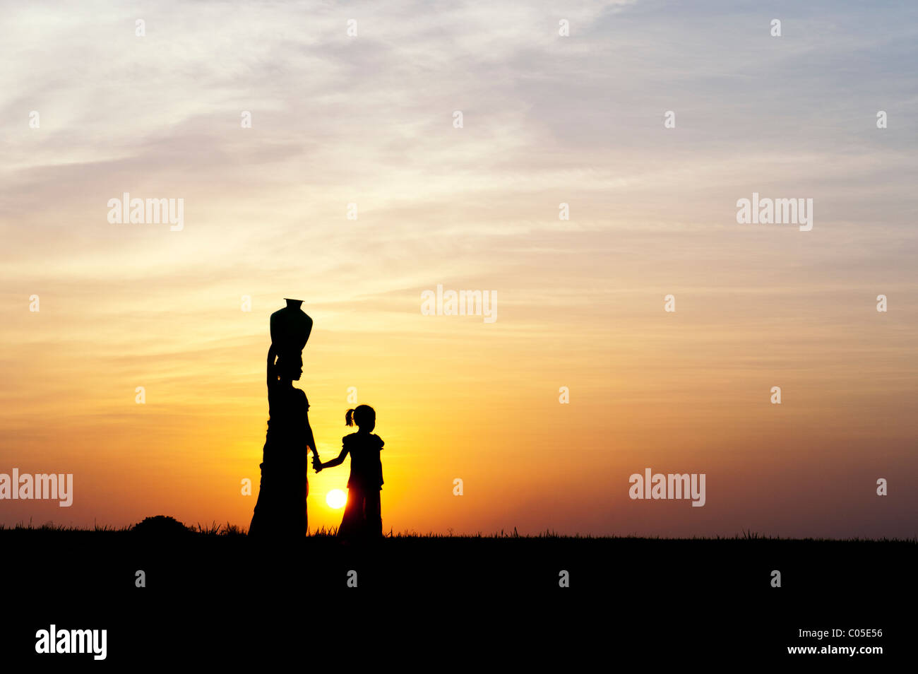 Indian mother carrying water pot with child in the indian countryside at sunset. Silhouette - Stock Image