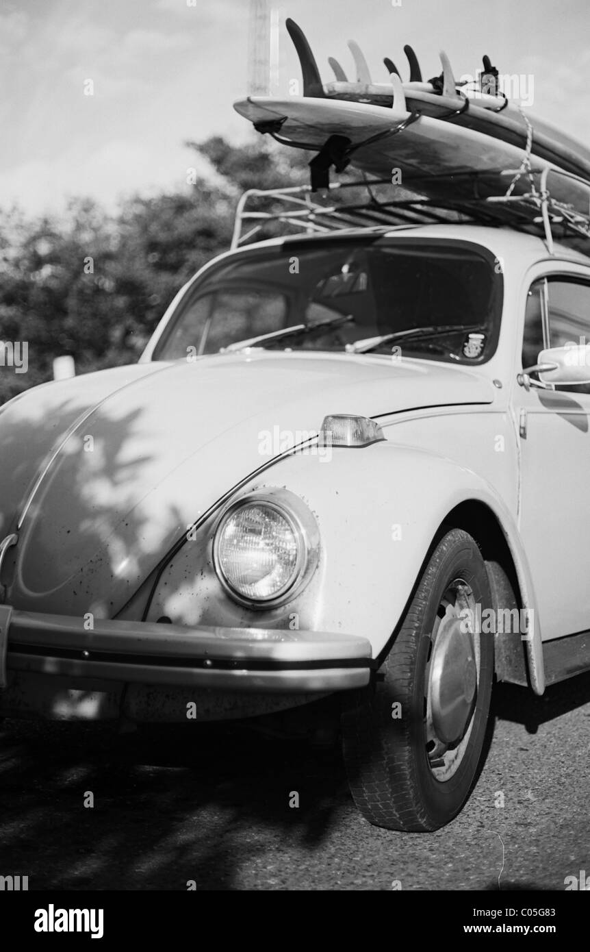 A VW Beetle gets loaded up to go surfing - Stock Image