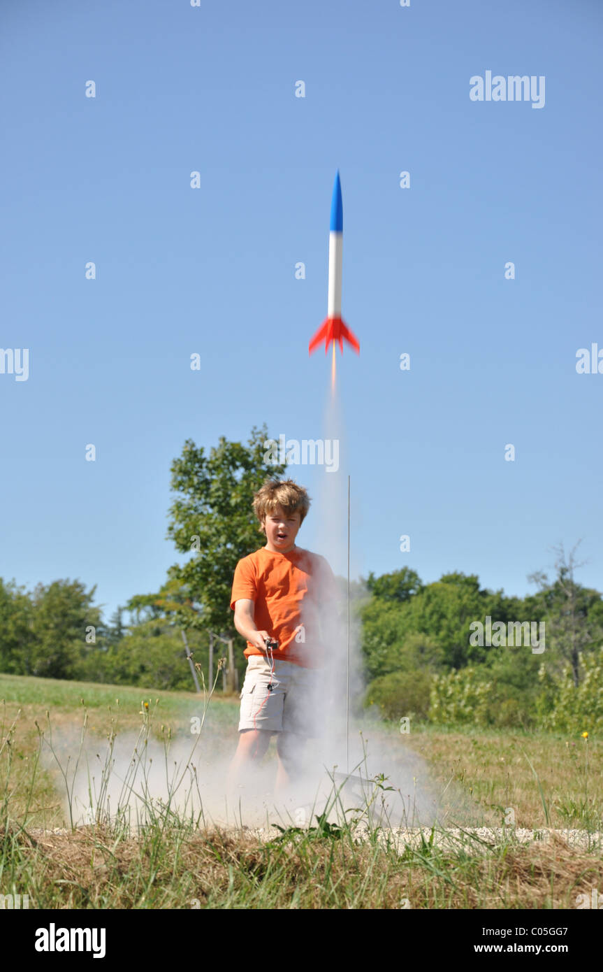 12 year old boy launches model rocket outside - Stock Image