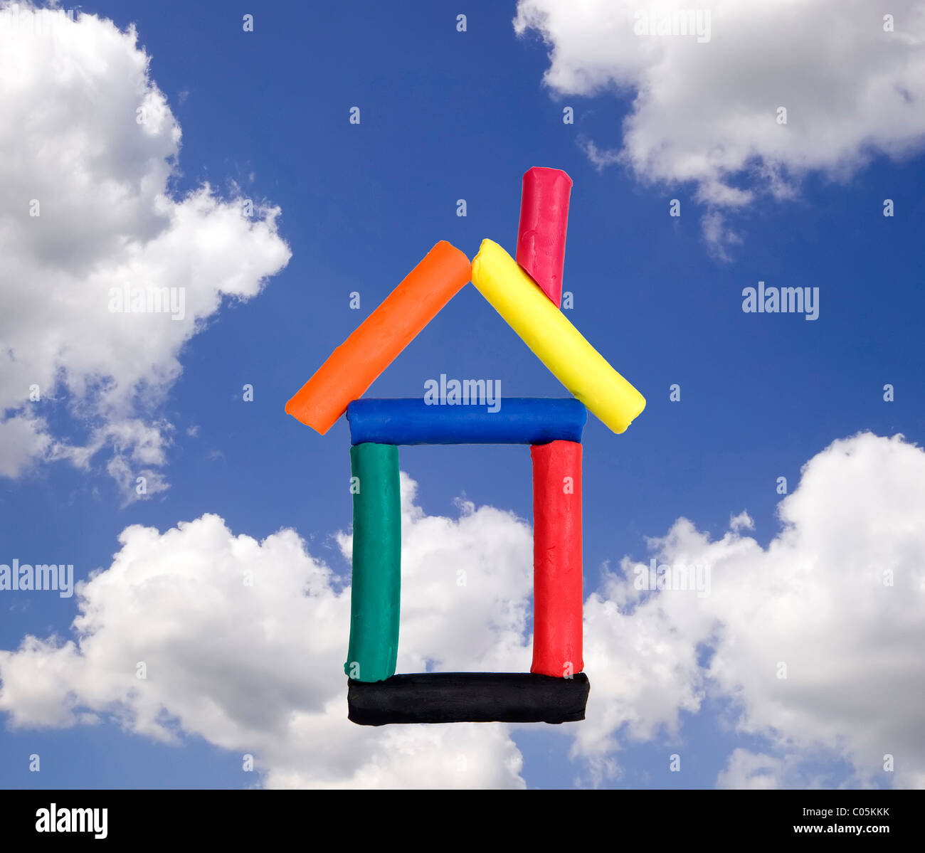 Funny house made from colorful plasticine on sky background - Stock Image
