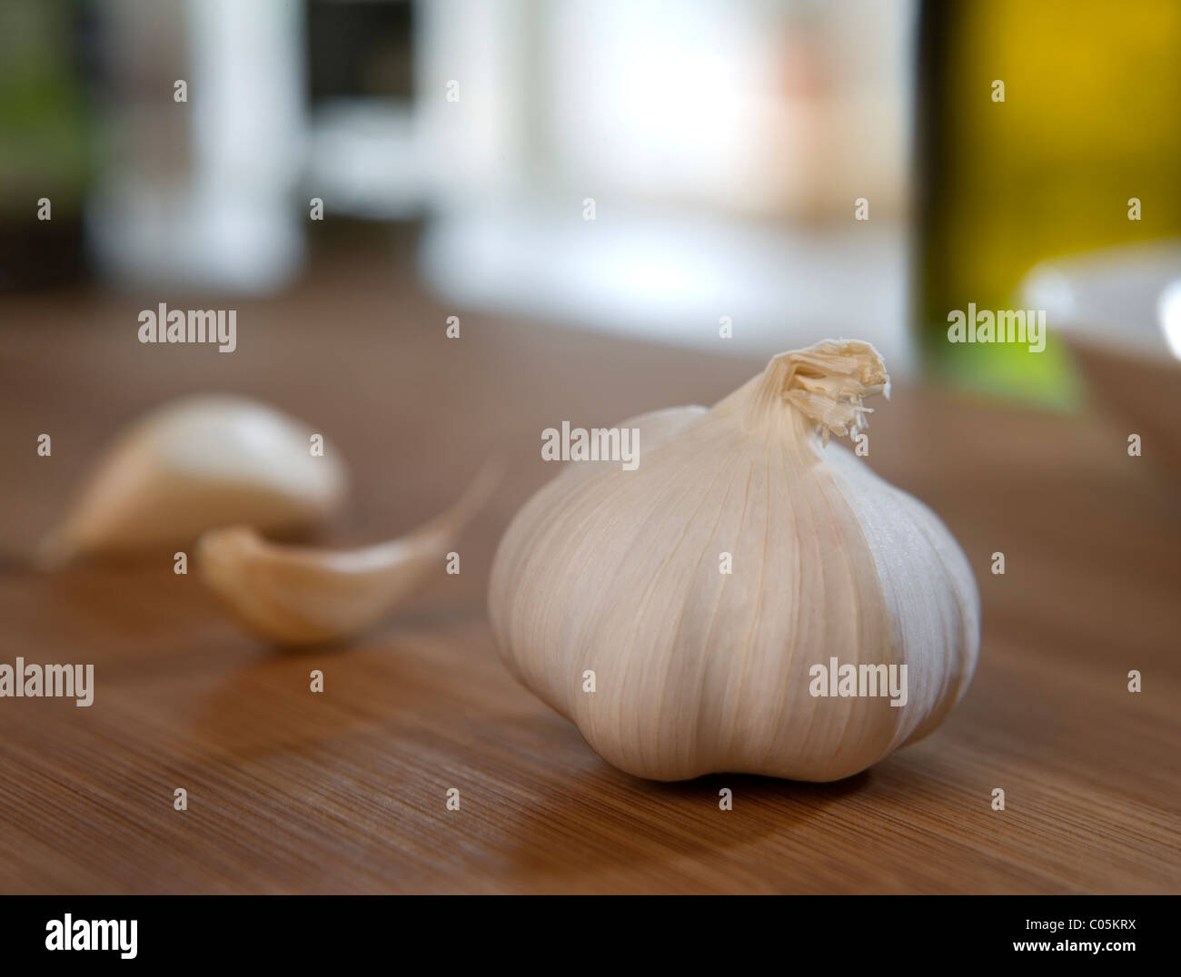 A head of garlic and 2 cloves on a cutting board - Stock Image