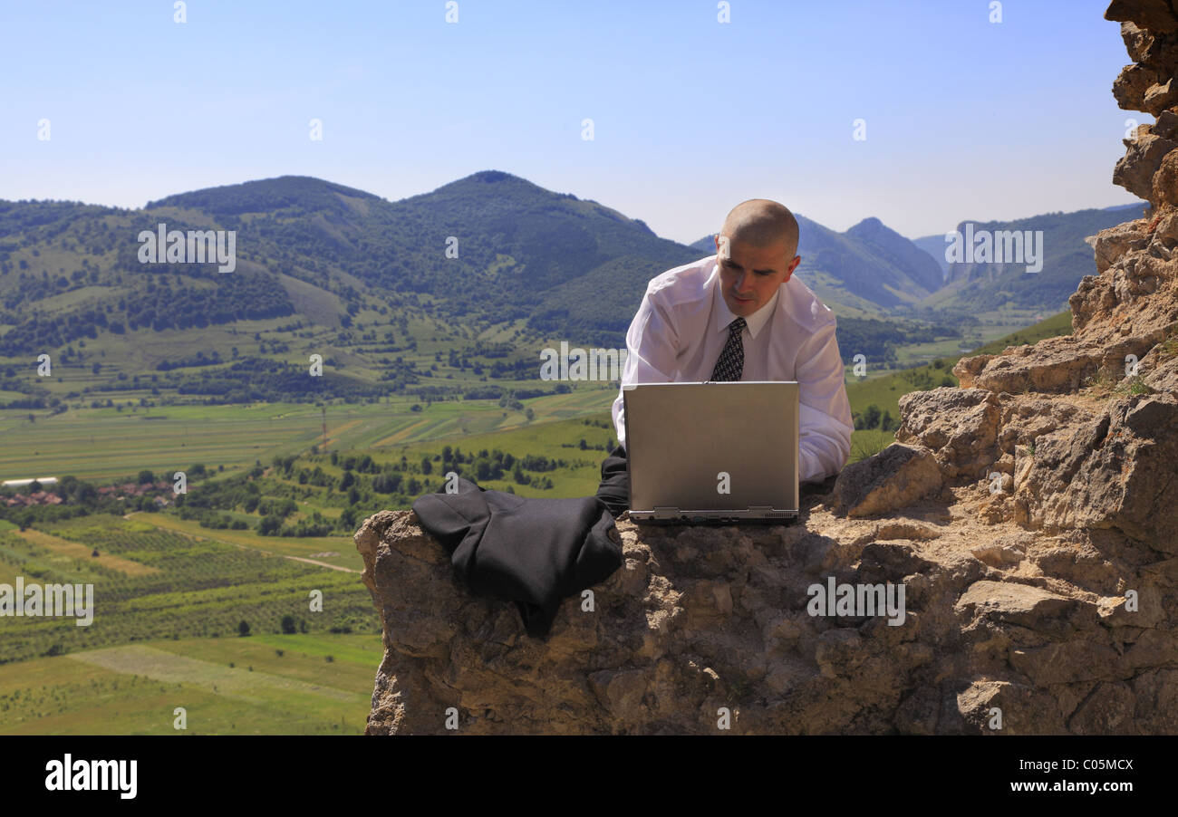 Businessman working on a computer outdoors. - Stock Image