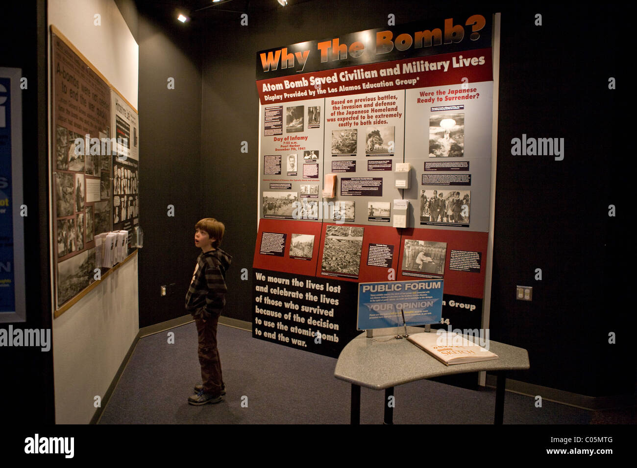 Eight year old child reading about World War II, Atomic bomb use in Hiroshima. 'Why the bomb?'  Science - Stock Image