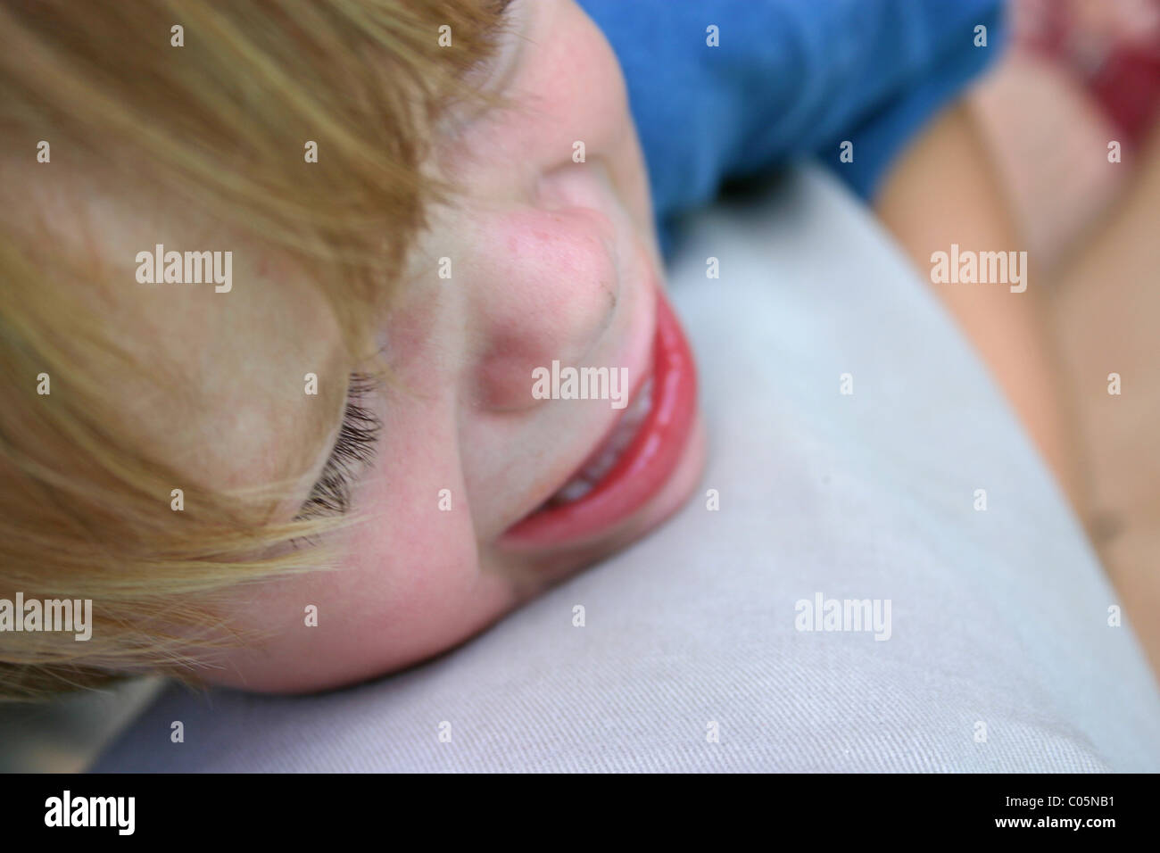 Two year old child clinging to parent, crying.  Parent's perspective, high angle view. - Stock Image