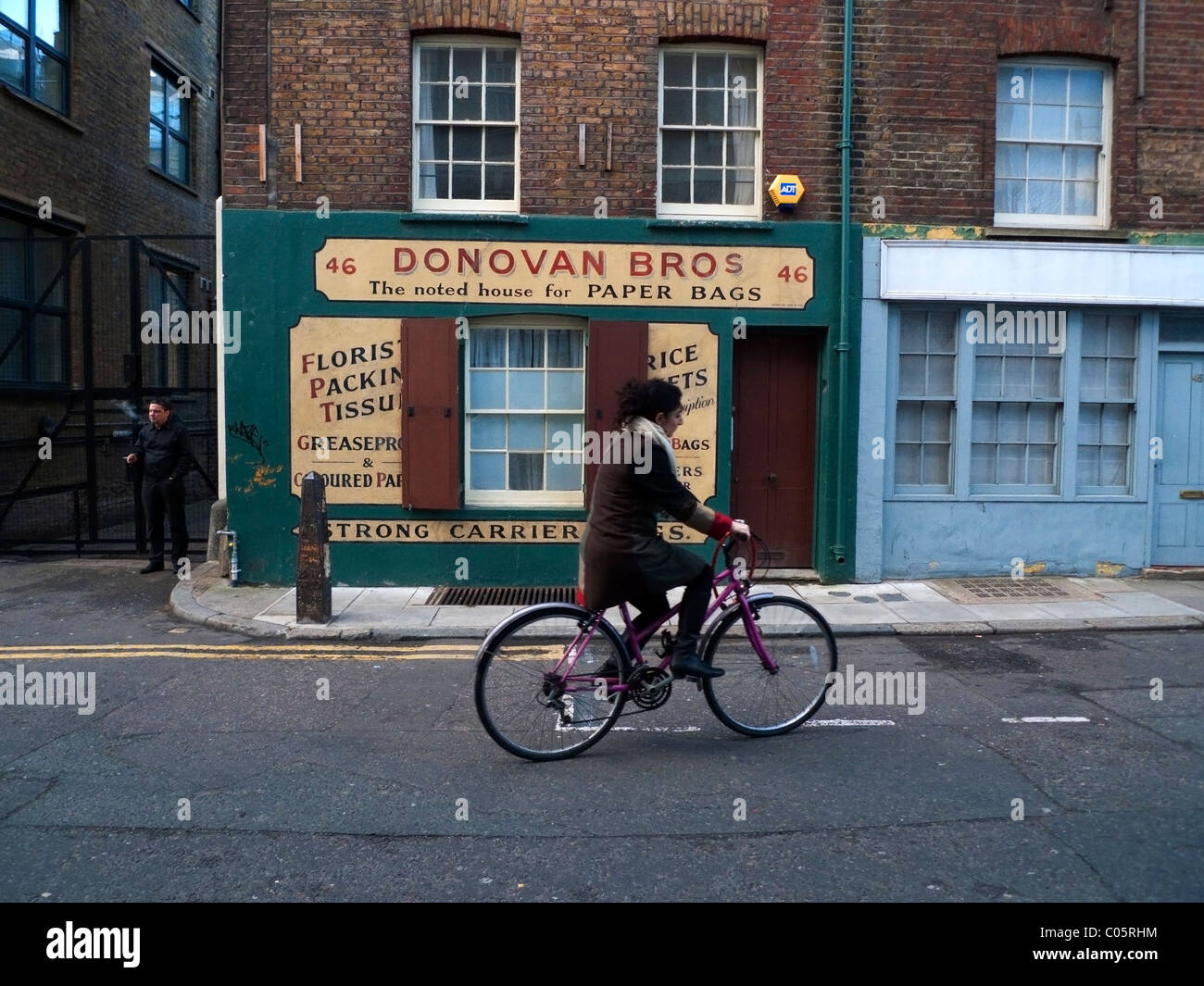 A woman on a bicycle cycling past Donovan Bros Paper Bag family business shop Spitalfields in East London UK  KATHY - Stock Image